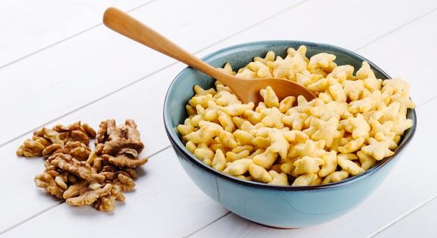 Seitenansicht von sternförmigen cornflakes in einer schüssel und walnüssen auf dem tisch