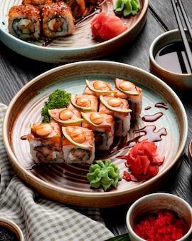 Seitenansicht von sushi-rollen mit garnelen-avocado und frischkäse, serviert mit ingwer und wasabi auf einem teller auf holz