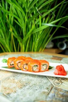 Seitenansicht von sushi-satzrollen mit krabbenfleisch-frischkäse und avocado im kaviar des fliegenden fisches auf grün
