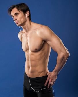 Seitenansicht von tragenden kopfhörern des hemdlosen mannes mit muskeln