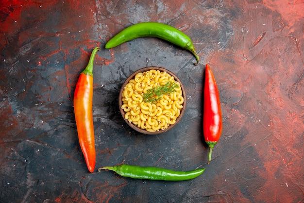 Seitenansicht von ungekochten nudeln in einer braunen schüssel und cayennepfeffer auf gemischtem farbtisch