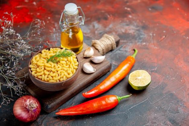 Seitenansicht von ungekochten nudeln in einer braunen schüssel und knoblauch auf hölzernem schneidebrett pfeffer zitronenzwiebel auf gemischter farbtabelle