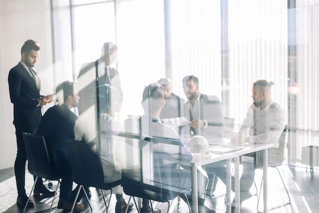 Seitenansicht von unscharfen silhouetten von geschäftsleuten, die im konferenzraum sprechen