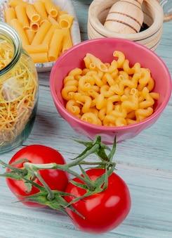 Seitenansicht von verschiedenen arten von makkaroni als cavatappi ziti spaghetti mit tomaten schwarzem pfeffer auf holztisch