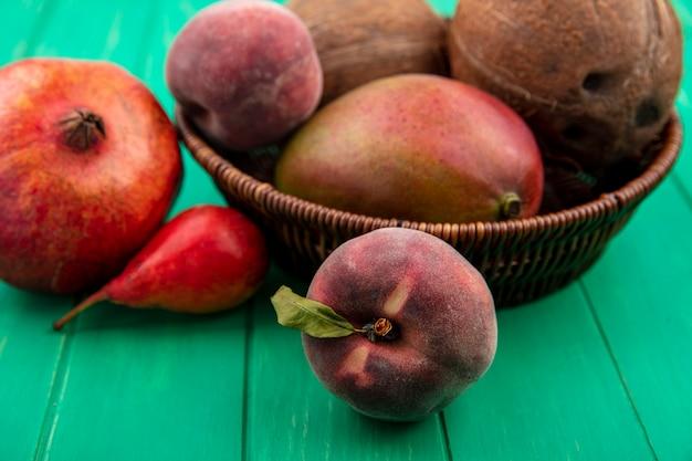 Seitenansicht von verschiedenen früchten wie kokosnuss-mango-pfirsich-granatapfel auf einem eimer auf grüner oberfläche
