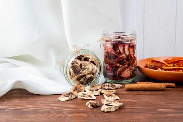 Seitenansicht von verschiedenen getrockneten geschnittenen früchten in gläsern banane und erdbeere auf holzhintergrund