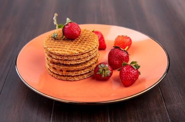 Seitenansicht von waffelkeksen mit erdbeeren im teller auf holz