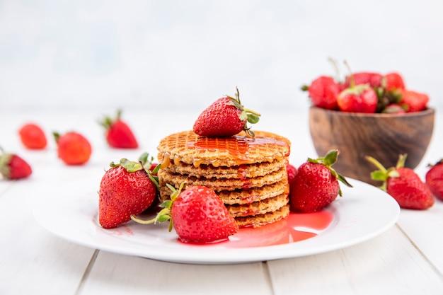 Seitenansicht von waffelkeksen mit erdbeeren in teller und in schüssel und auf holz