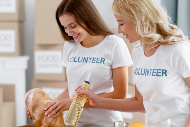 Seitenansicht von weiblichen freiwilligen, die lebensmittel für die spende vorbereiten
