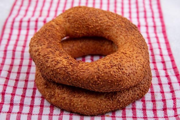 Seitenansicht von weichen und knusprigen traditionellen türkischen bagels auf einem rot karierten tuch auf einem weißen hintergrund