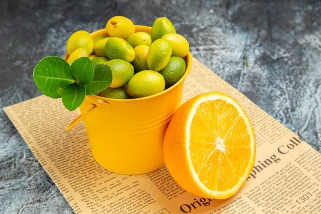 Seitenansicht von zitrusfrüchten auf zeitung auf grauem hintergrund kumquats und orange stockfoto