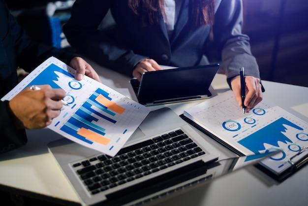 Seitenansicht von zwei college-mädchen, die an ihrer aufgabe mit laptop- und tablet-planung von investitionsprojekten und strategie für gespräche mit partner und beratung im büro arbeiten