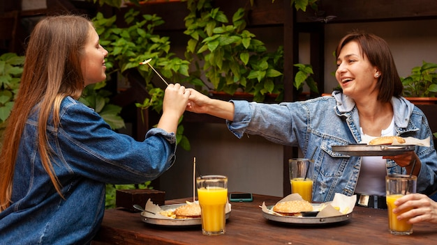 Seitenansicht von zwei frauen, die sich gegenseitig burger füttern