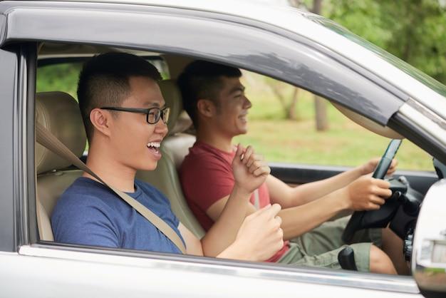Seitenansicht von zwei sorglosen kerlen, die im auto betriebsbereit zu einer autoreise sitzen