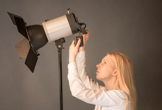Seitenansicht weiblicher fotograf, der die lampe einstellt