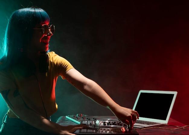 Seitenansicht weibliches dj, das audiokonsole überprüft