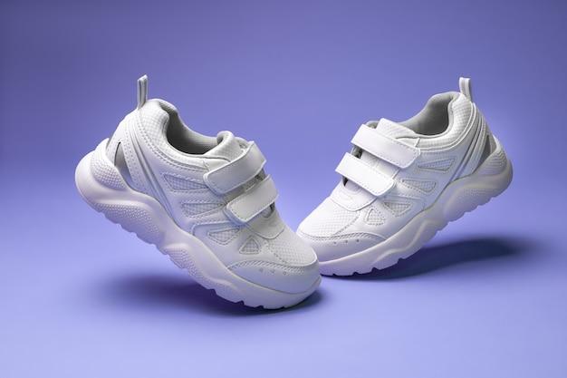 Seitenansicht weiße unisex-sneaker mit klettverschluss fliegen in der luft zehen zu einander isoliert auf lila hinter...