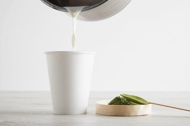 Seitenansicht zum mitnehmen von weißem papierglas und hochwertigem bio-japan-matcha-tee auf holztisch bereit für die moderne latte-zubereitung. präsentation dritter schritt. etwas heiße milch auf glas verderben.