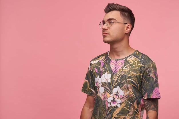 Seitenansichtaufnahme des ernsten hübschen jungen mannes, der geblümtes t-shirt und brille trägt, nachdenklich beiseite schauend, mit händen unten stehend