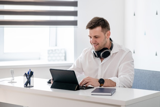 Seitenansichtaufnahme des nachdenklichen jungen mannes, der zu hause sitzt und am laptop arbeitet. kaukasischer mann, der vom hauptbüro arbeitet.