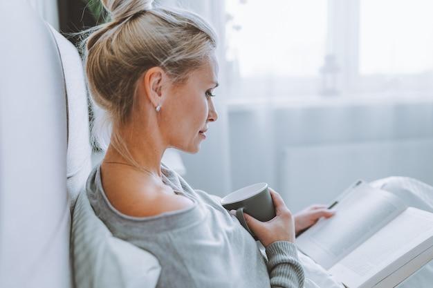 Seitenansichtaufnahme einer attraktiven jungen frau, die auf ihrem bett sitzt und einen interessanten roman liest. kaukasisches weibliches modell im schlafzimmer, das ein buch liest.