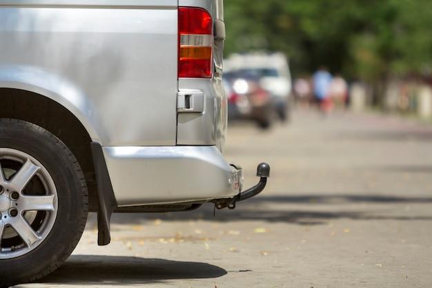 Seitenansichtdetail der nahaufnahme des mittelgroßen luxuskleinbuspackwagens des silbernen passagiers mit anhängerkupplung parkte auf sonniger stadtstraßenpflasterung des sommers