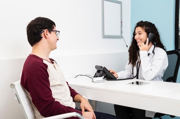 Seitenansichtdoktor, der am telefon spricht