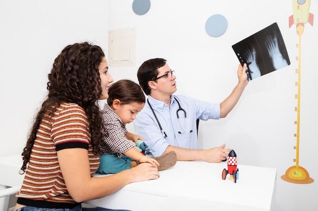 Seitenansichtdoktor, der eine radiographie hält