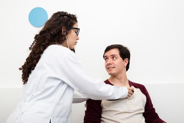 Seitenansichtdoktor, der patienten überprüft