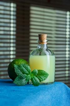 Seitenansichtflasche zitronensaft mit blättern und grüner zitrone auf schwarzer fensteroberfläche. vertikaler kopierraum für text