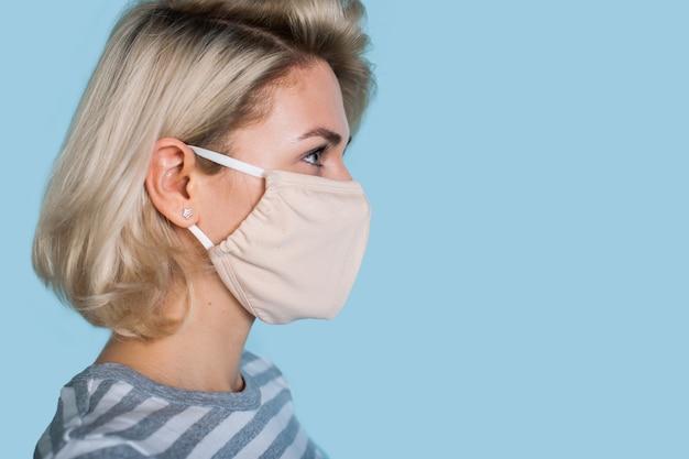 Seitenansichtfoto einer blonden kaukasischen frau, die eine medizinische maske trägt, die auf den blauen freien raum nahe ihr schaut