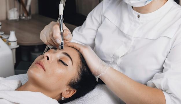 Seitenansichtfoto einer kaukasischen frau, die spezielle hautbehandlungen auf ihrem gesicht in einem spa-salon hat