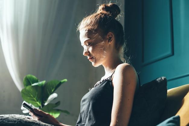 Seitenansichtfoto einer kaukasischen ingwerfrau, die papiermaske trägt, die im bett liegt