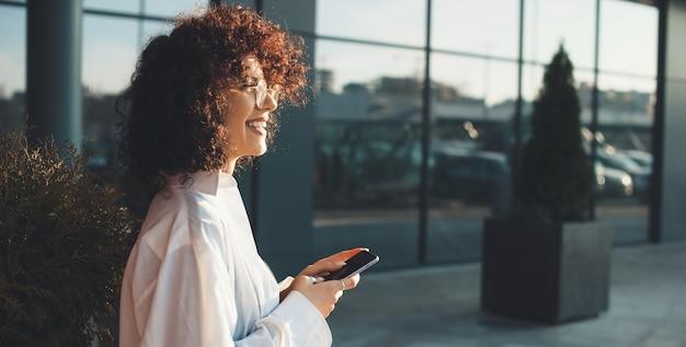 Seitenansichtfoto eines lockigen unternehmers, der lächelt und eine brille trägt, während er am telefon außerhalb nahe einem modernen büro plaudert