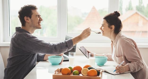 Seitenansichtfoto eines paares, das sich gegenseitig füttert, während es einen laptop mit tablette benutzt und früchte isst