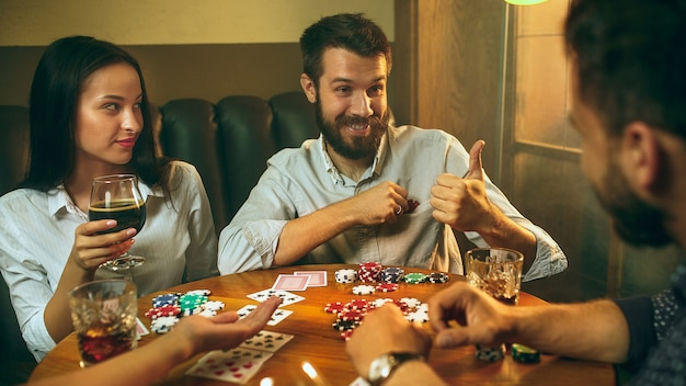 Seitenansichtfoto von freunden, die am holztisch sitzen. freunde, die spaß beim brettspiel haben.
