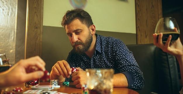 Seitenansichtfoto von männlichen freunden, die am holztisch sitzen. männer spielen kartenspiel. hände mit alkohol nahaufnahme.