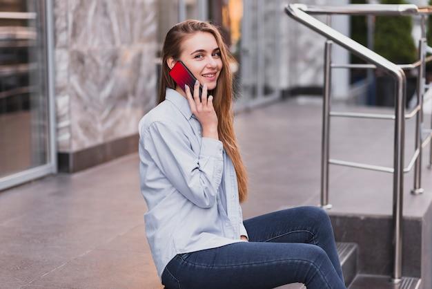 Seitenansichtfrau auf treppe sprechend über telefon