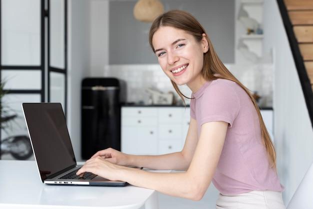 Seitenansichtfrau, die an ihrem laptop arbeitet