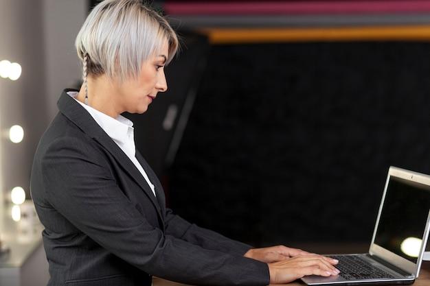 Seitenansichtfrau, die an laptop arbeitet