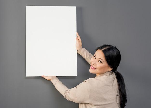 Seitenansichtfrau, die auf wand balnk papierblatt sich setzt