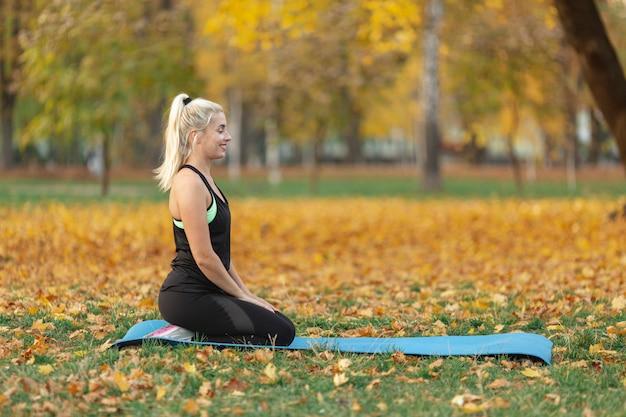 Seitenansichtfrau, die auf yogateppich sitzt