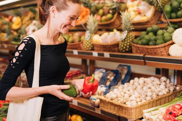 Seitenansichtfrau, die avocado und grünen pfeffer hält
