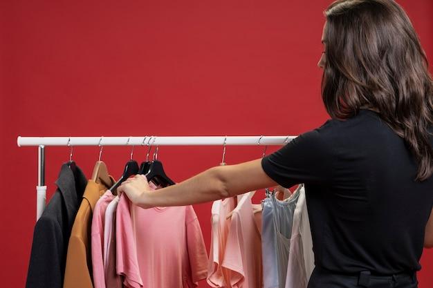 Seitenansichtfrau, die durch t-shirts schaut