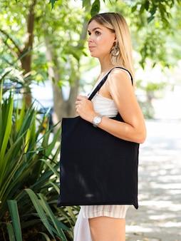 Seitenansichtfrau, die eine schwarze tasche hält