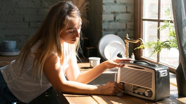 Seitenansichtfrau, die einen alten radio verwendet