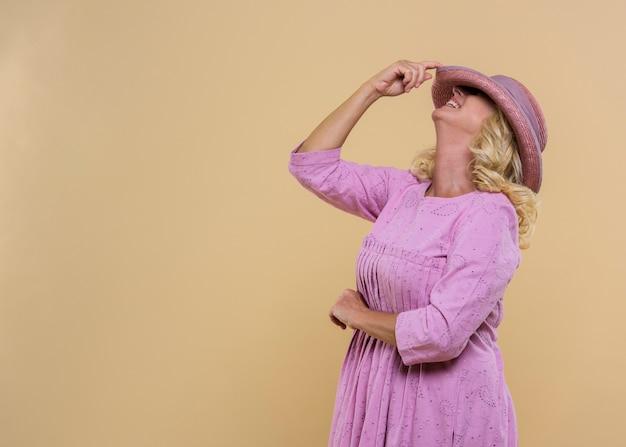 Seitenansichtfrau, die einen rosa hut mit kopienraum trägt
