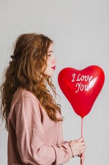Seitenansichtfrau, die einen valentinstagballon hält