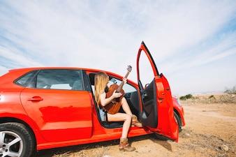 Seitenansichtfrau, die Gitarre im Auto spielt