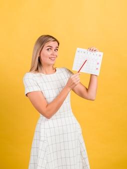 Seitenansichtfrau, die ihren zeitraumkalender zeigt